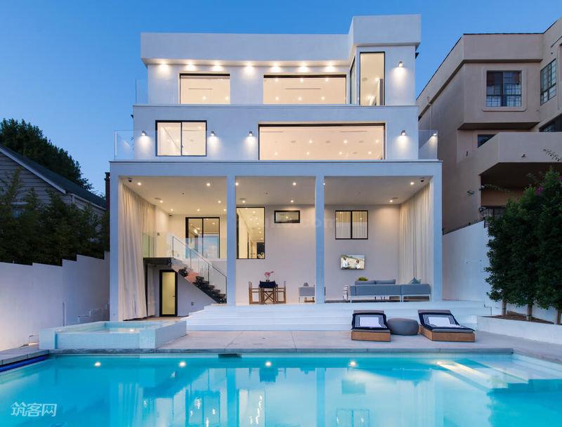 現代別墅裝修風格外形方正簡潔、功能強,在造型上有一種簡約、通透和凌厲的感覺。在空間布局、顏色搭配以及整體的空間視覺效果上具有大氣、簡約、隨意的感覺。  現代泳池別墅設計案例:這款簡約現代的三層別墅設計上,方正簡潔,線條干凈利落,四面通透采光極好,具有開放性的特點。燈光的設計錯落有致,輝映在蔚藍清澈的泳池里,宛如月光寶盒一般通透。  現代泳池別墅設計案例:室內設計采用黑白簡約配色,沙發和茶幾,采用簡潔的幾何造型,沒有多余的顏色和多余的修飾。淺灰色的地毯十分低調,和墻上的黑白壁畫靜靜地呼應著。燃氣壁爐的方正造